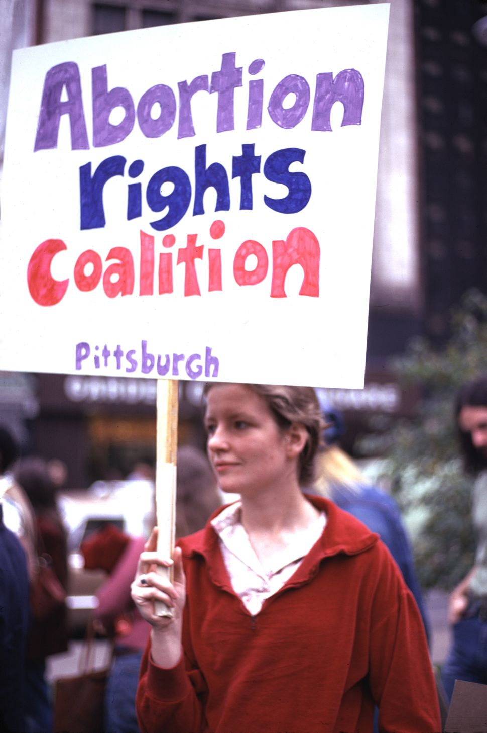 "<strong>1974:</strong> A young woman holds a sign reading ""Abortion Rights Coalition"" during a 1974 reproductive rights demon"