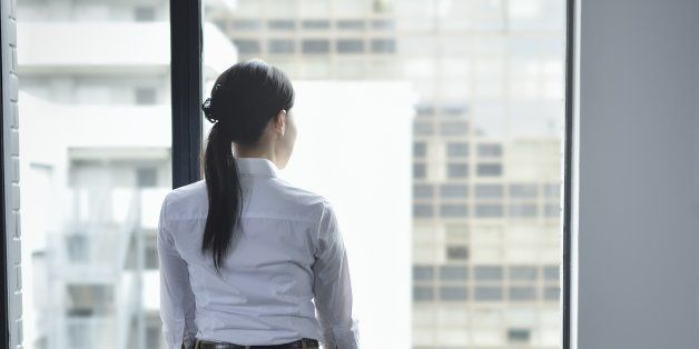 Businesswoman looking out window in empty office