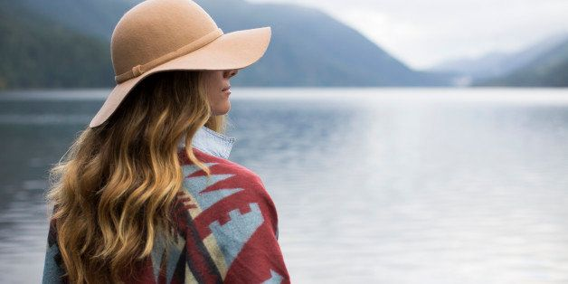 A woman with a floppy hat and native shall overlooking a lake.
