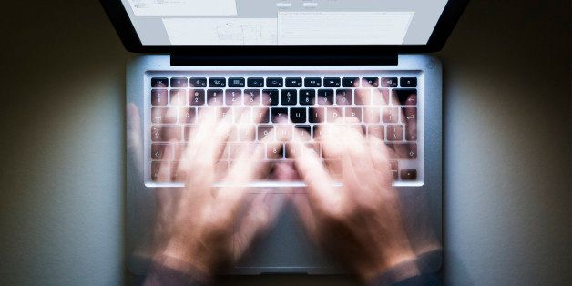 Laptop, speed typing, screen glowing in the dark