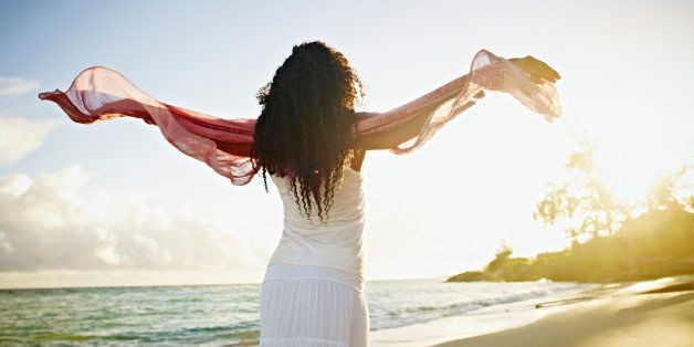 Woman on tropical beach at sunrise with arms outstretched towards sun