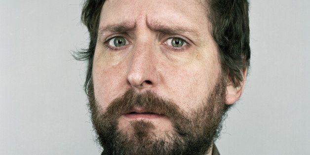 A bearded man frowns with a questioning look