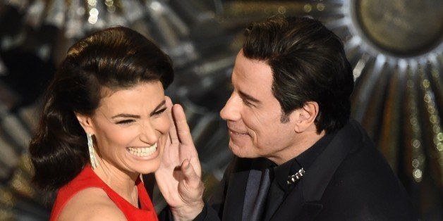 John Travolta (R) and Idina Menzel present an award on stage at the 87th Oscars February 22, 2015 in Hollywood, California. A