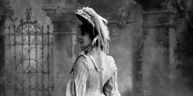 Miss Mansfield wearing a full sleeved coatdress, with lace detail, and a feather trimmed hat.