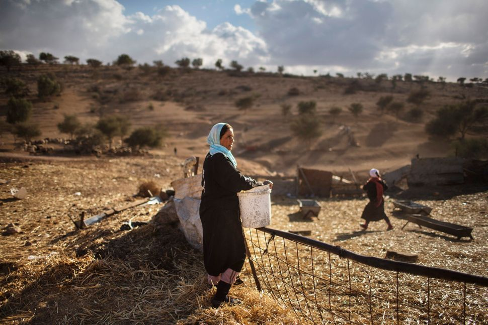 A Bedouin woman of the Al-Qiyaan tribe stands while working outside her house on Dec. 5, 2013 At the Bedouin village of Umm A
