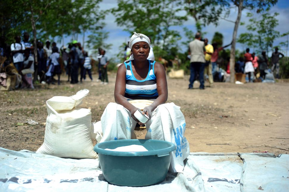 A woman distributes salt in Baie des Moustiques, Port de Paix in Haiti on April 3, 2014. (HECTOR RETAMAL/AFP/Getty Images)