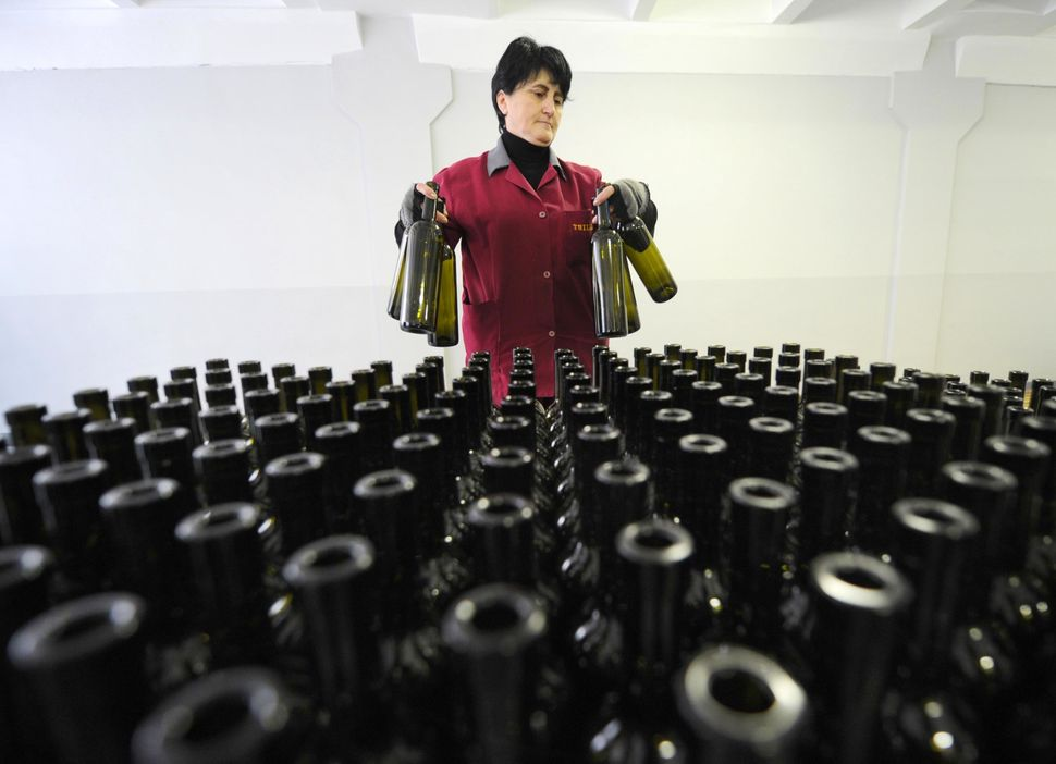 An employee stands in front of bottles at a winery in Tbilisi on Feb. 11, 2013.  (VANO SHLAMOV/AFP/Getty Images)