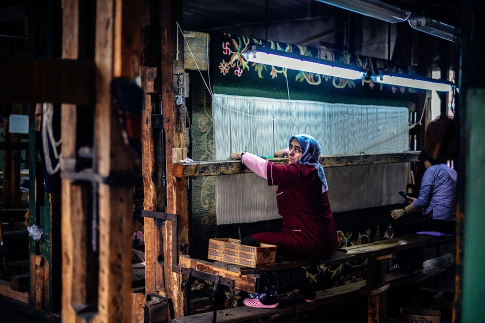 Photo taken on January 22, 2014, shows women working on a carpet in a tiny factory in Kostandovo, a small village in Bulgaria