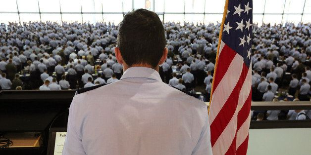 A junior officer reads the names of U.S. troops recently killed in action to cadets standing at attention before the start of