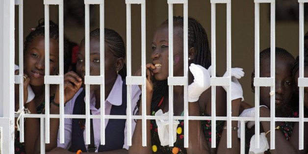 School girls look watch first lady Michelle Obama and Senegal's first lady Madame Marieme Faye Sall during a visit to the all