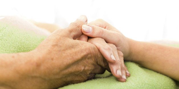 Social services nurse holding elderly woman's hand with care.
