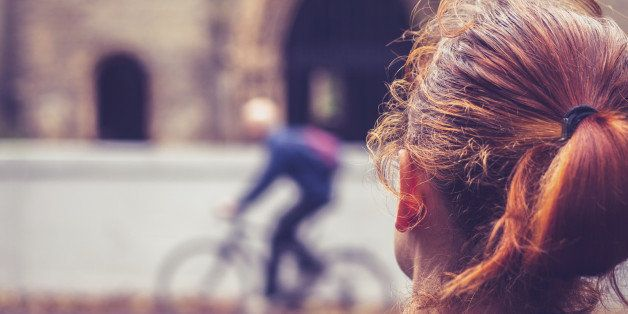 Rear view of a young woman looking at a church and a person on a bicycle