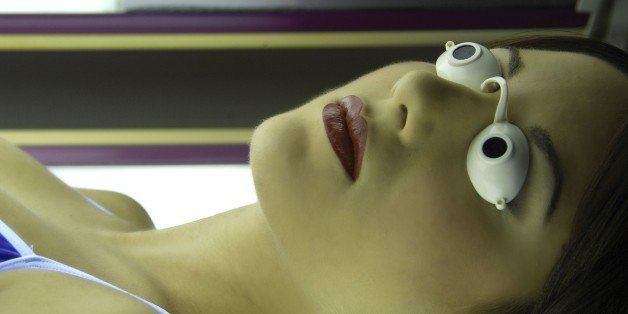 A young woman lying in a tanning capsule