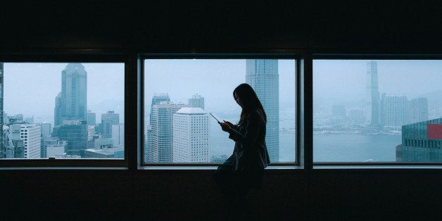 Office lady is using tablet with city view from windows at background