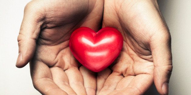 Two hands cup a heart in a caring and loving way. The heart symbolises love and relationships