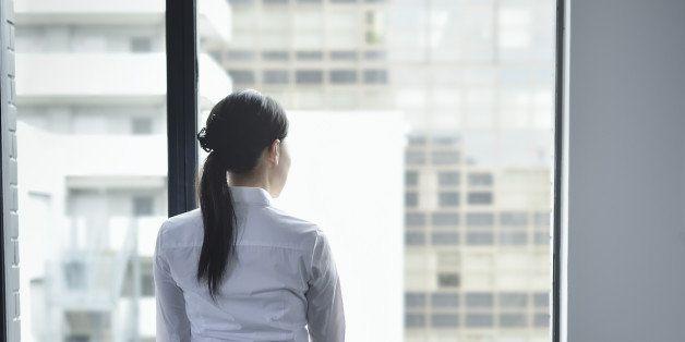Businesswoman looking out window in empty office