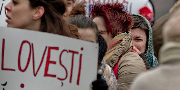 Women shout slogans outside the city hall during a protest in Bucharest, Romania, Tuesday, Nov. 25, 2014. Romanian women gath