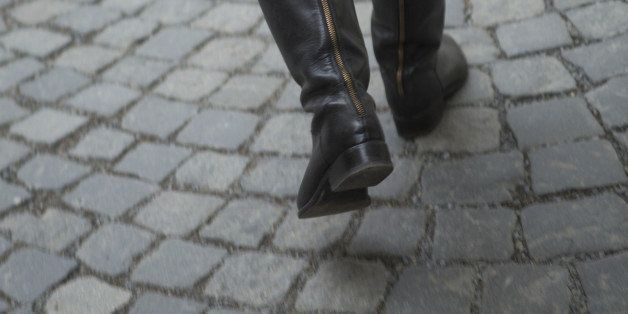 Rear view of woman's knee-high boots as she walks across stone courtyard in Prague.