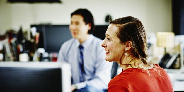 Smiling businesswoman in discussion with coworker at workstation in office