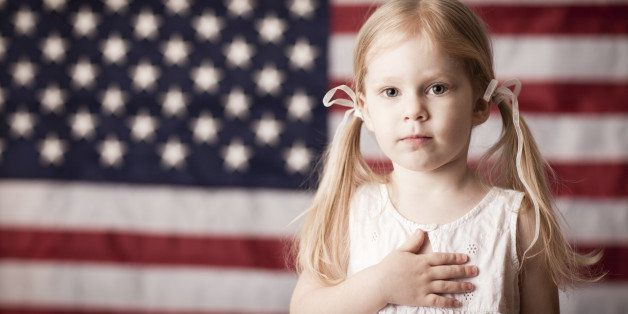 Color photo of a little blond-haired girl with her hand on her heart in front of an American flag.