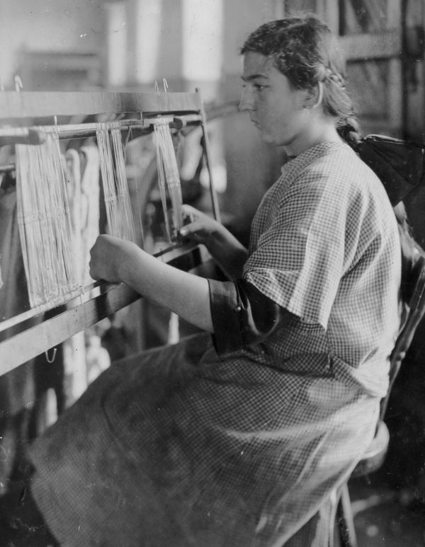 A young woman works as a harness maker at the American Linen Company, in Fall River, MA, 1916.