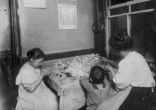 A thirteen-year-old girl (identified only as Mary) works with her aunt as they make flowers in a tenement room, New York, New