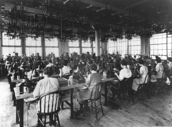 View of women factory workers seated at their work stations while operating machines to polish lenses, during the early twent
