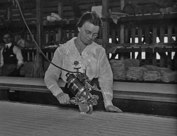 A woman machine operator working with a cutting tool at an aircraft factory during World War 1.