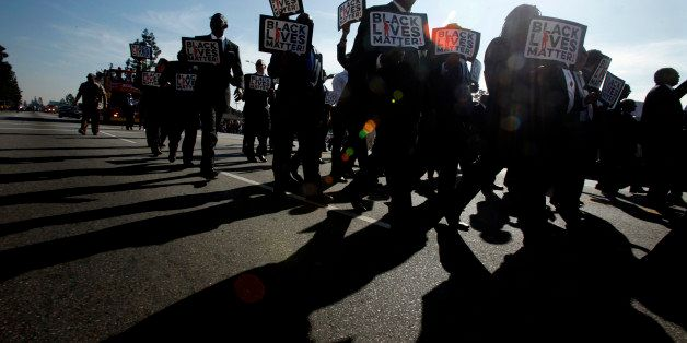 LOS ANGELES, CA - JANUARY 19: Men in Suits carrying signs that state, 'Black Lives Matter!' march in the 30th Annual Kingdom