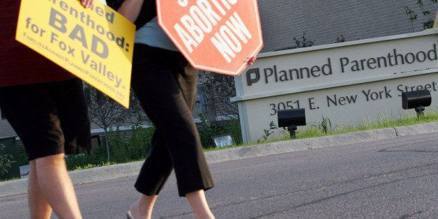FILE - In this Sept. 18, 2007 file photo, protesters march near a Planned Parenthood location in Aurora, Ill. Some Illinois l