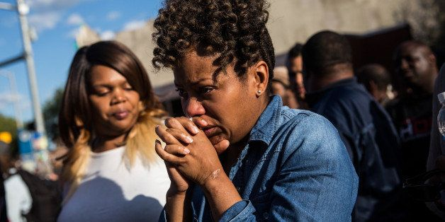 BALTIMORE, MD - APRIL 28:  A woman cries after being prayed over during a protest near the CVS pharmacy that was set on fire