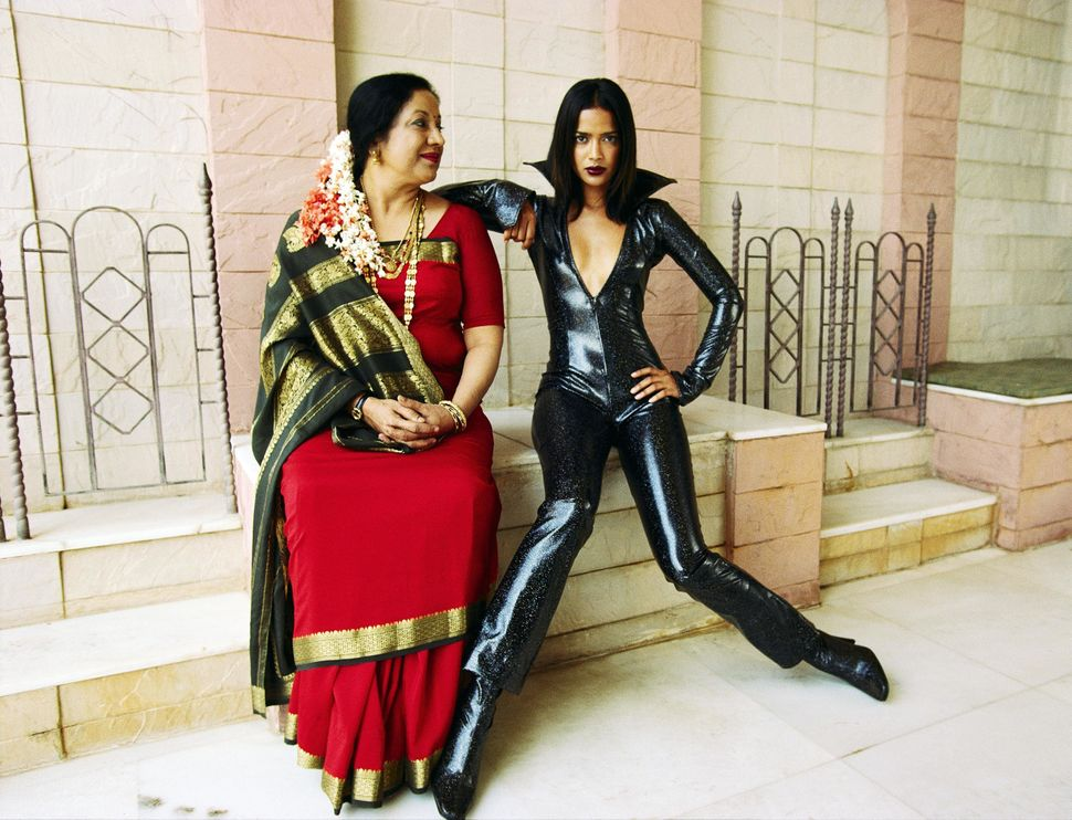 Indian mother poses with model daughter in contrasting outfits; the mother in traditional Indian garments while the daughter