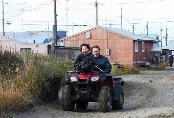 Mother and daughter ride an all-terrain vehicle in Shishmaref, Alaska on September 26, 2006.