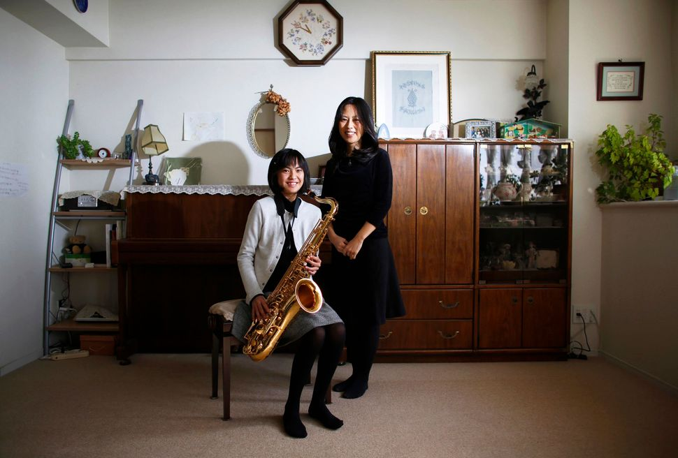 Manami Miyazaki, 39, and her daughter Nanaha, 13, holding her alto saxophone, pose for a photograph at their home in Tokyo, J