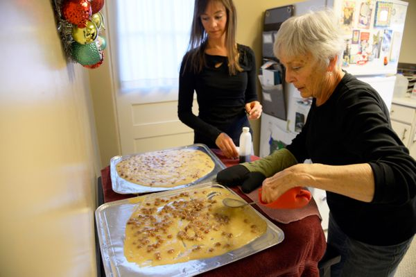 Julie Becker spreads brittle mixture with her daughter Laura Becker, on trays as they make candy with a recipe for brittle th