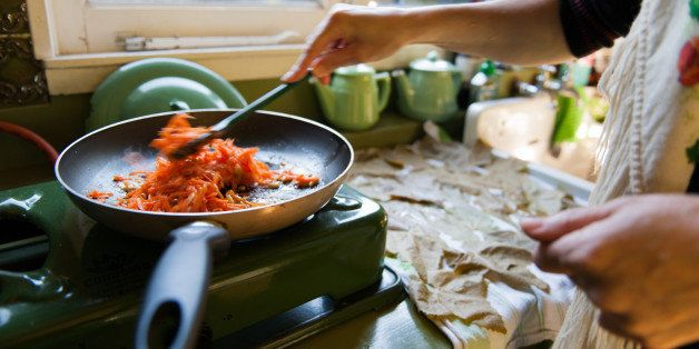 Frying pan on old fashioned gas stove, with carrots and rice. Woman is stirring the ingredients. Wine leaves are drying on a