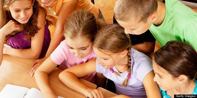 Cute Little school children having class with laptop, sitting around 2 school girls typing in focus, in the classroom