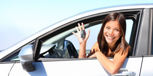 Asian car driver woman smiling showing new car keys and car. Mixed-race Asian and Caucasian girl.