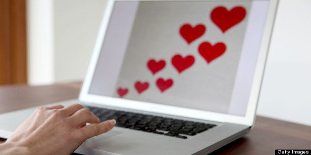 A woman's hand on a laptop keyboard with red hearts on the screen.