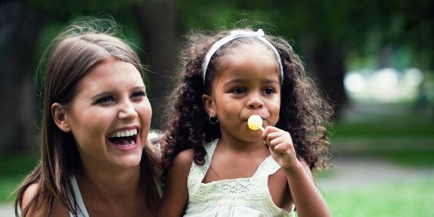 white woman in her 20's playing in the park, with an african american little girl. colorful, high contrast images.