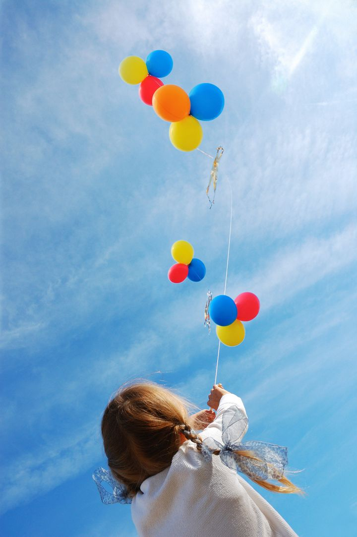 child flying colorful balloons in the blue sky