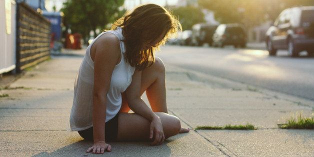 A girl sits on the sidewalk at sunset in Long Beach, NY.