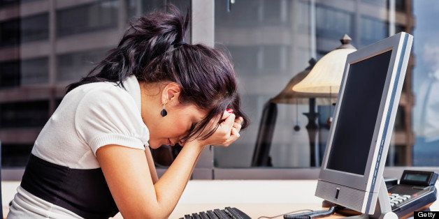 Photo of a businesswoman sitting at her desk with her head in her hands, as if having a very bad day.