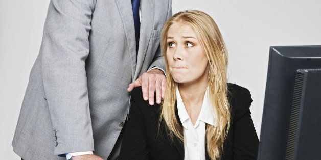 A  businessman stands behind a pretty and vulnerable young businesswoman, leaning over her with one hand on her shoulder as s