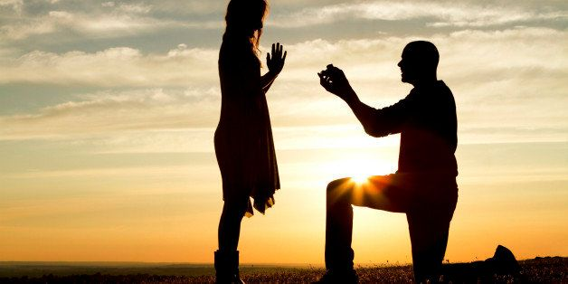 Silhouette of a man proposing marriage to a woman against the setting sun