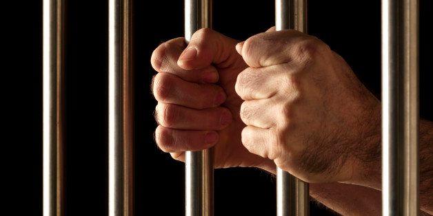 hands of a prisoner behind bars