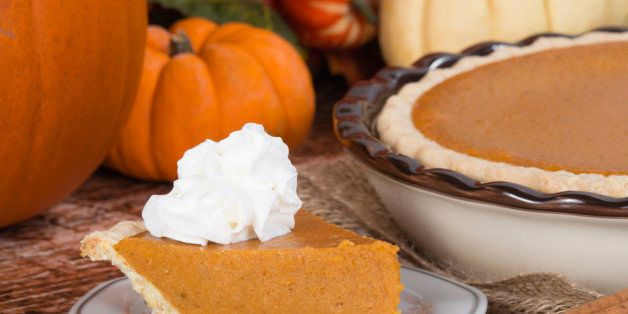 Slice of a pumpkin pie with whipped cream on wooden table. Pie and pumpkins on the background.