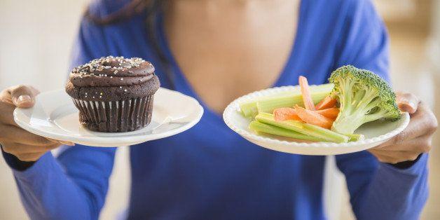 Mixed race woman choosing vegetables or cupcake