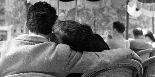 23rd June 1951:  A young couple sharing an intimate moment in one of the pavement cafes on the Champs-Elysees, Paris. Origina