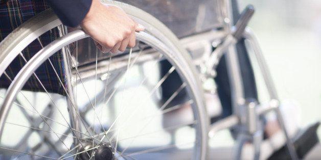 Woman turning wheel of wheelchair